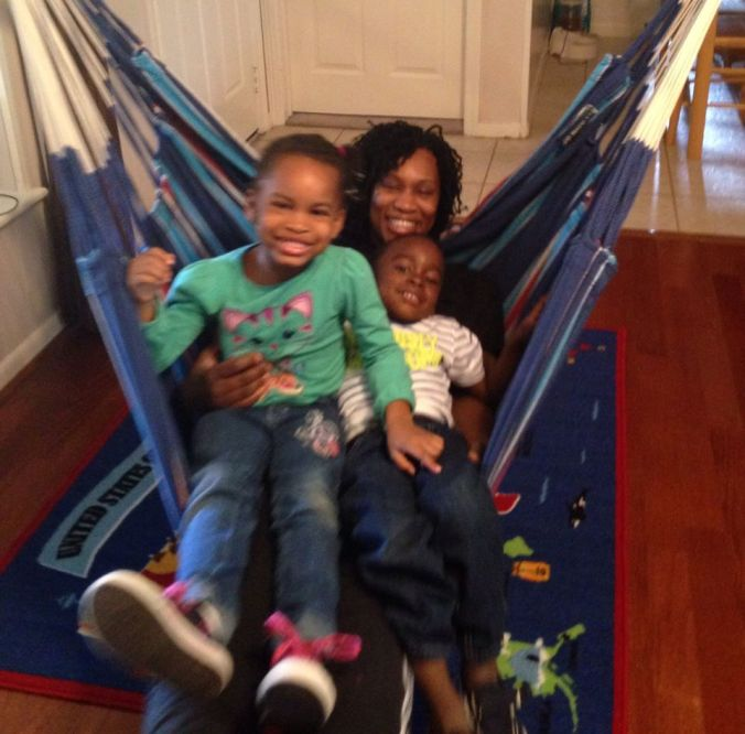 A family shot of a woman with two young children sitting piled together on an indoor hammock.